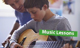 Boy being taught guitar by teacher
